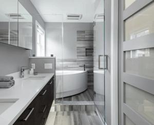 Modern master bathroom with floating vanity, arched bathtub, glass door and pocket door.