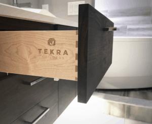Custom walnut vanity with engraved TEKRA Builders logo on dovetail drawer