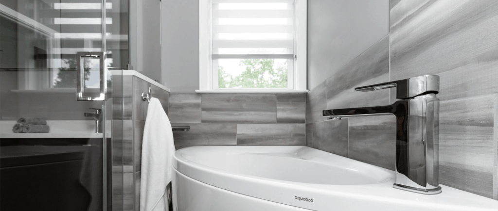 Arched Corner tub with gray wall tile and window