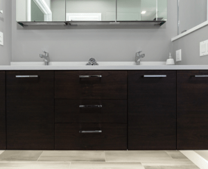 Custom floating walnut vanity with undercabinet lighting and double sinks
