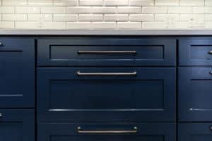 Long cabinet handles on blue cabinets with white beveled subway backsplash