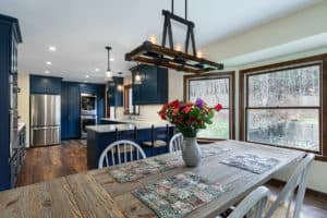 Rustic chandelier with dining room table and blue kitchen