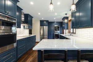 Blue kitchen with white quartz countertops and subway backsplash