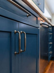 Blue kitchen cabinets with iron hardware handles