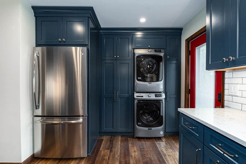 Washer and dryer built into cabinetry with fridge.