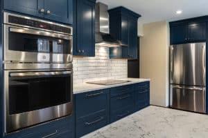 Double wall oven, range hood and stainless steel fridge.