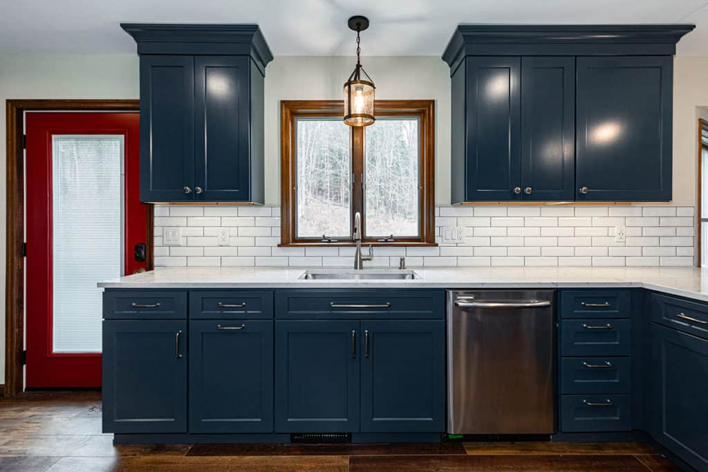 Blue cabinets with white countertops and beveled subway backsplash
