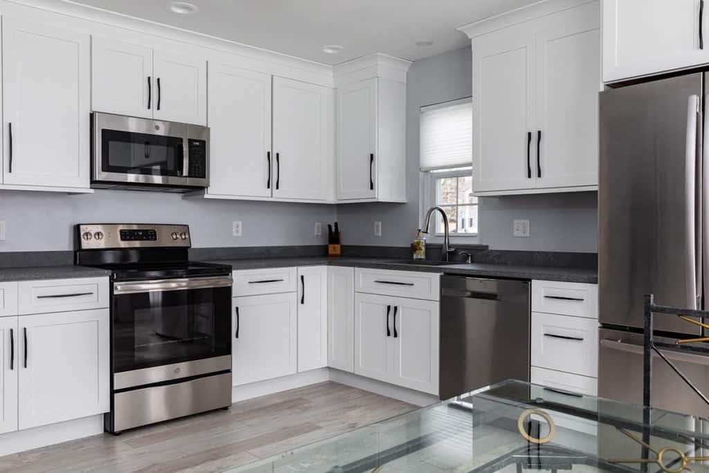 White shaker kitchen with gray walls and stainless appliances