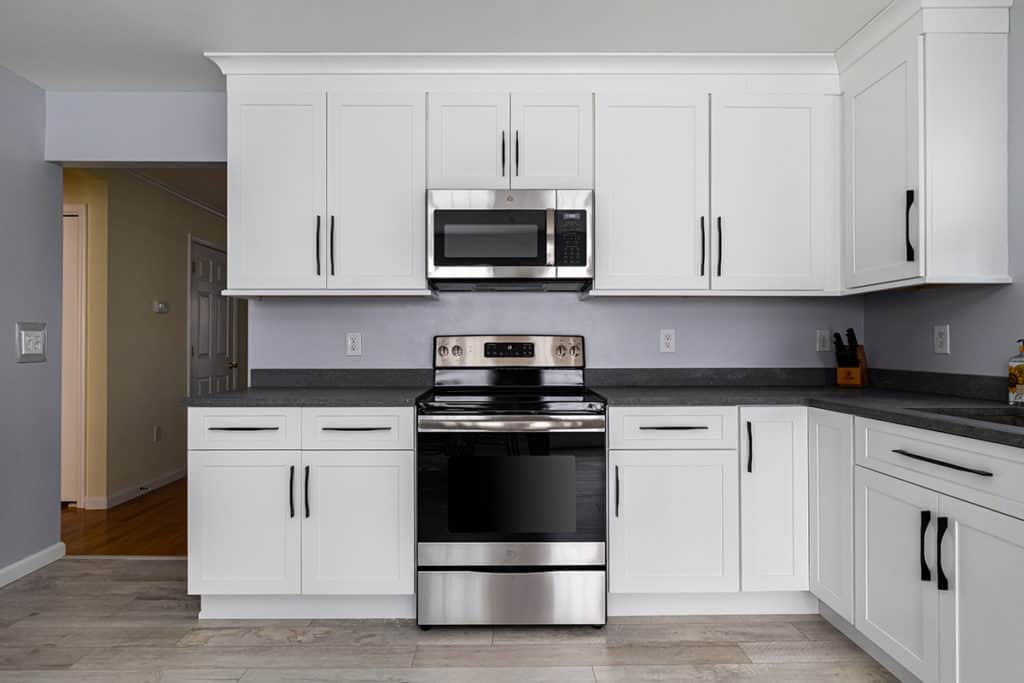 Kitchen with stainless and black oven, white LVP floors and concrete countertops.