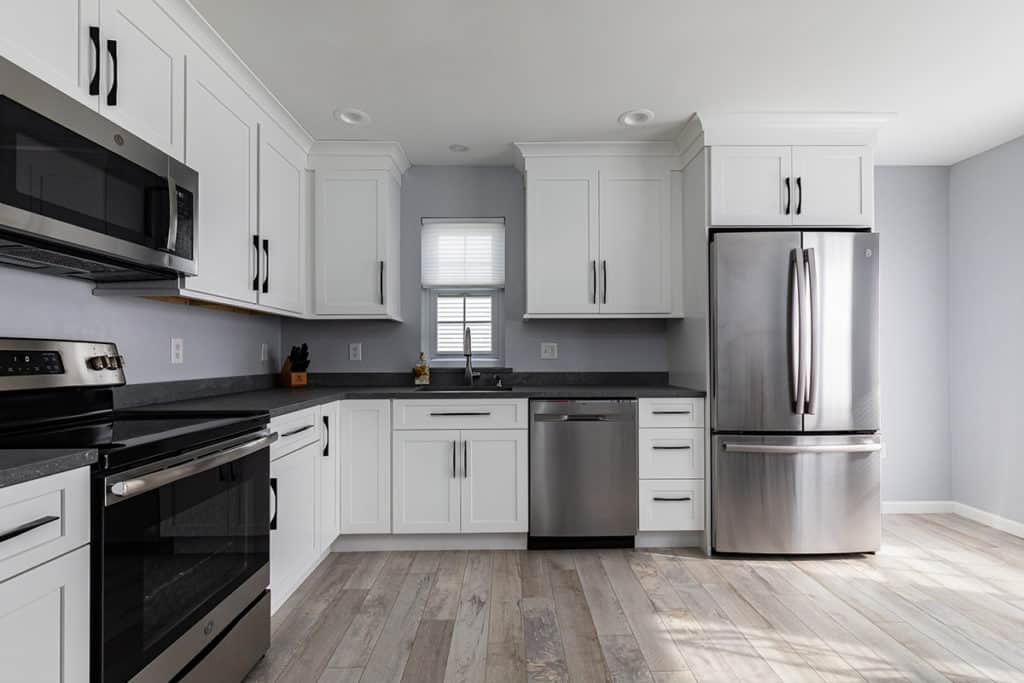 Kitchen with white shaker cabinets, stainless appliances and dark countertops.