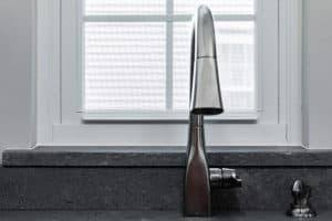 Concrete countertop window sill an d sink faucet.