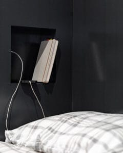 Cubby for storing books and charging phone incorporated into cabinetry.