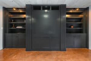 A murphy bed in the closed position with entertainment center and built in shelving.