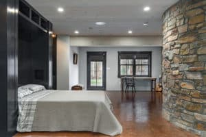 A murphy bed in the open position in basement man cave with curved stone wall.