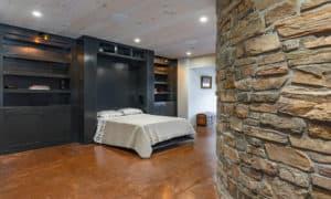 A queen-sized murphy bed built into basement man cave.