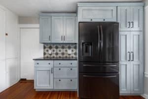 Blue kitchen cabinetry, black refrigerator and sunburst backsplash.