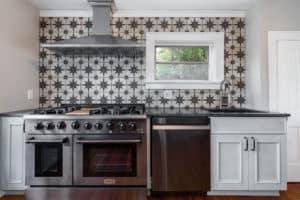 Sunburst backsplash, kitchen cabinets and black stainless appliances.