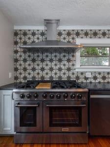 Black stainless steel Thor double oven range and freestanding range hood.