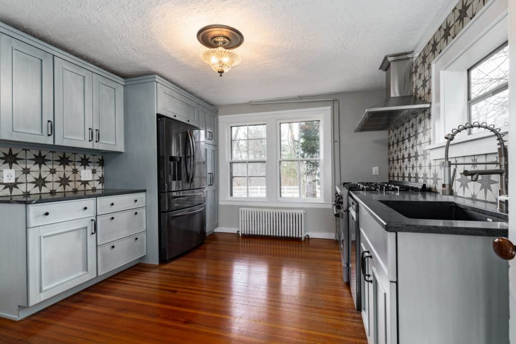Kitchen with blue cabinets, pine hardwood floors and black appliances
