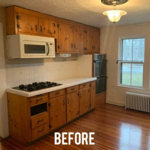 Old kitchen with pine cabinets and flooring, radiator, window and plaster texture ceiling